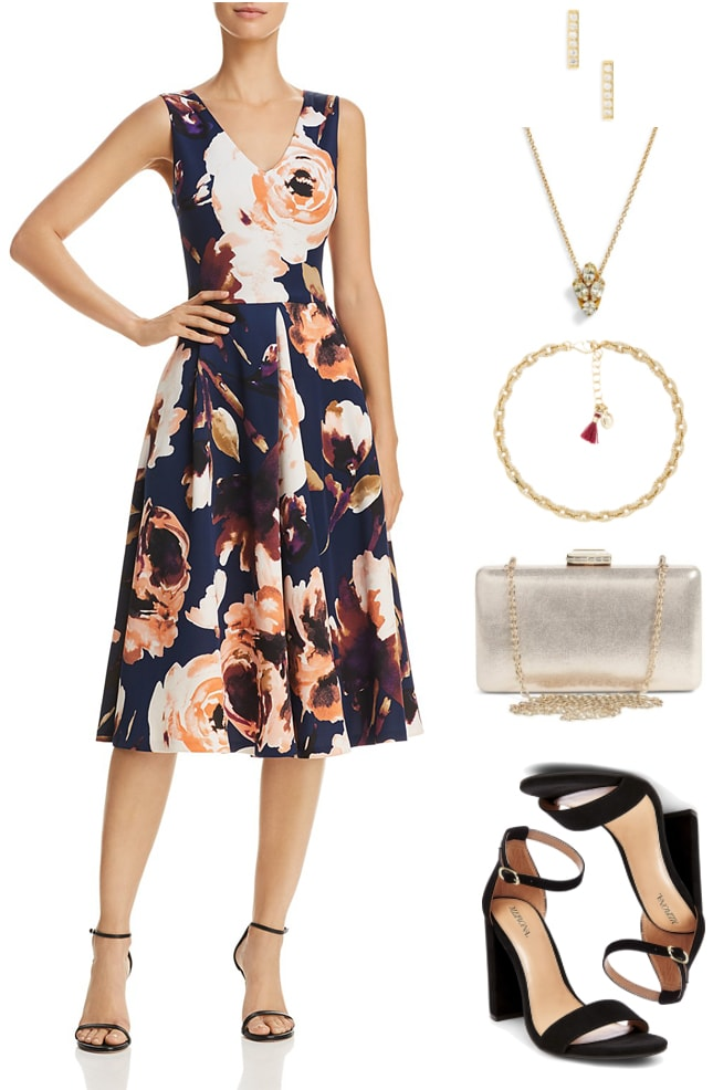 Navy blue sleeveless fit-and-flare midi-length dress with v-neck and large floral print, gold bar stud earrings with clear stones, gold necklace with clear stone pendant, gold bracelet with small pavé clear stone links and light red tassel, pale gold box clutch with chain strap, clasp with clear stones, and gold hardware; black block-heel sandals with ankle strap