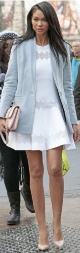 Chanel Iman wearing a white dress and powder blue coat