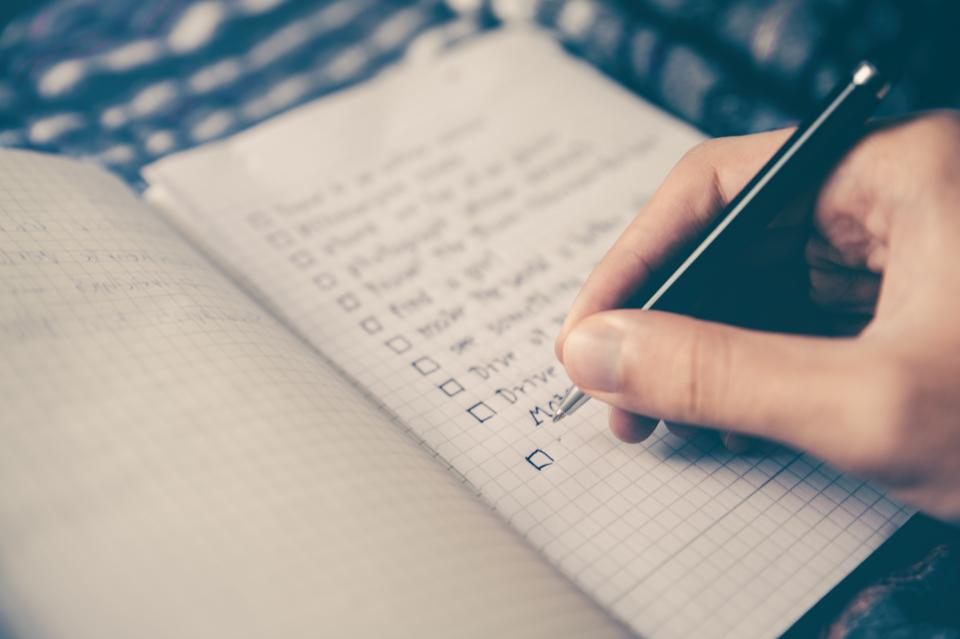 Person writing checklist on grid paper