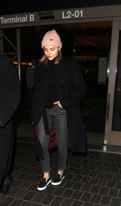 Chloe Moretz wearing a blush pink knit beanie hat, black sweater, long black coat, gray straight leg jeans, and black Vans slip on sneakers
