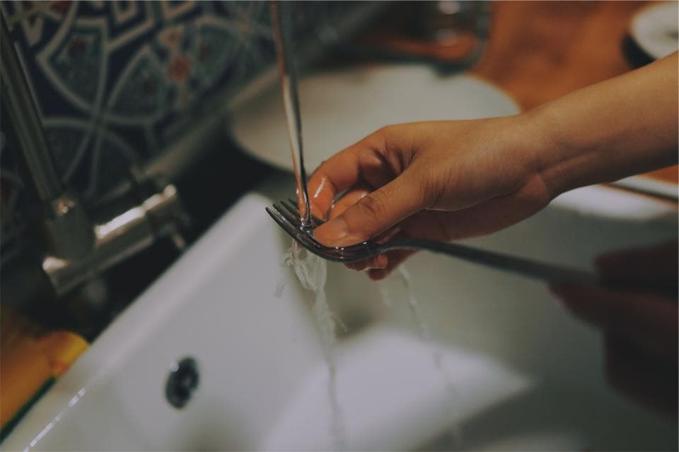 Photo of person washing a fork. Colorful tile in background as well as a dirty plate.