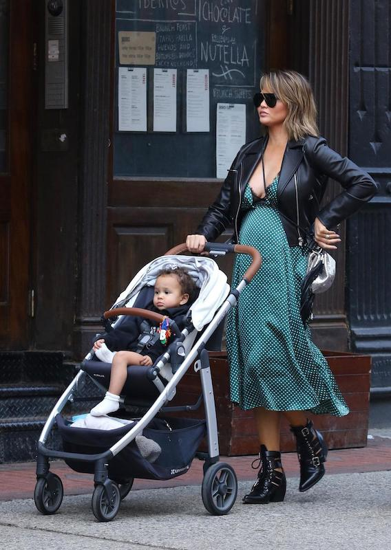 Chrissy Teigen wearing a black leather moto jacket, a green and white v-neck polka dot midi dress, black shield sunglasses, a silver and black tassel crossbody bag, and black leather lace-up booties