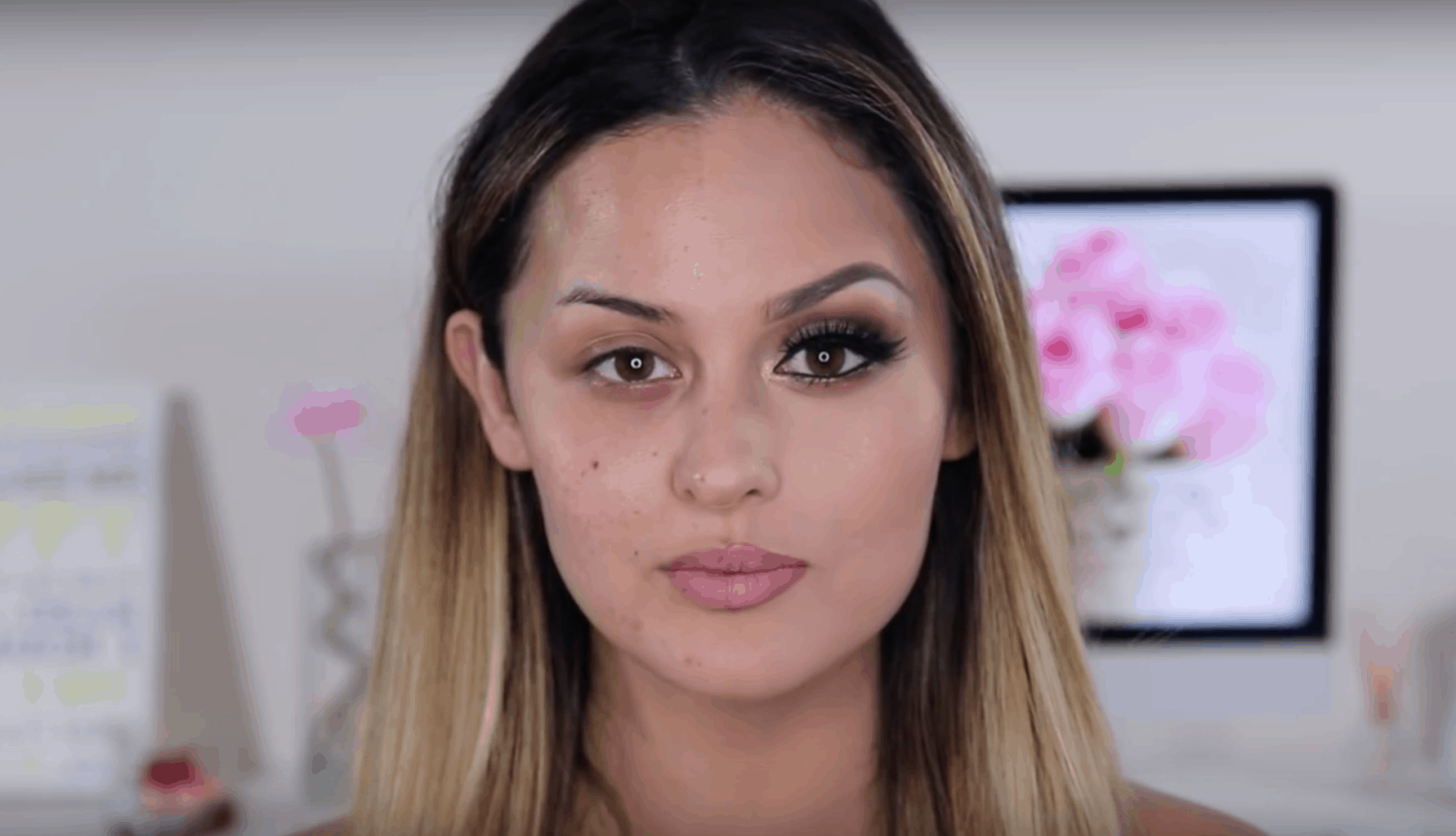 A beauty blogger wearing makeup on half of her face and no makeup on the other half