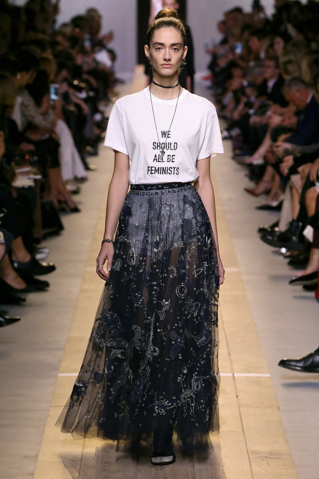 Dior Spring 2017 look 2: Model wearing a We Should All Be Feminists tee shirt, navy embroidered tulle skirt, and chokers