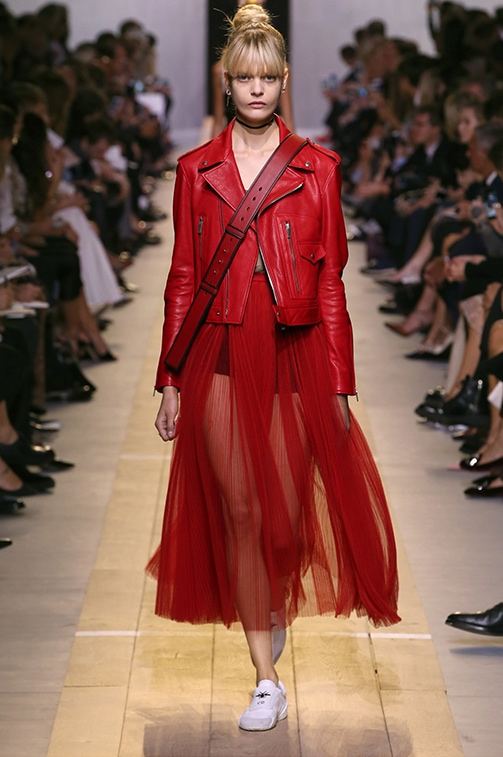 Dior Spring 2017 look 3: Red leather biker jacket worn over a red tulle pleated skirt and white sneakers