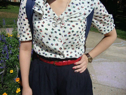 College fashionista wearing a patterned blouse and red belt