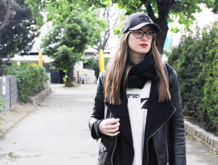 College student at University of Vienna wearing an edgy style black leather jacket, band tee shirt, hoodie, glasses, red lipstick and baseball cap