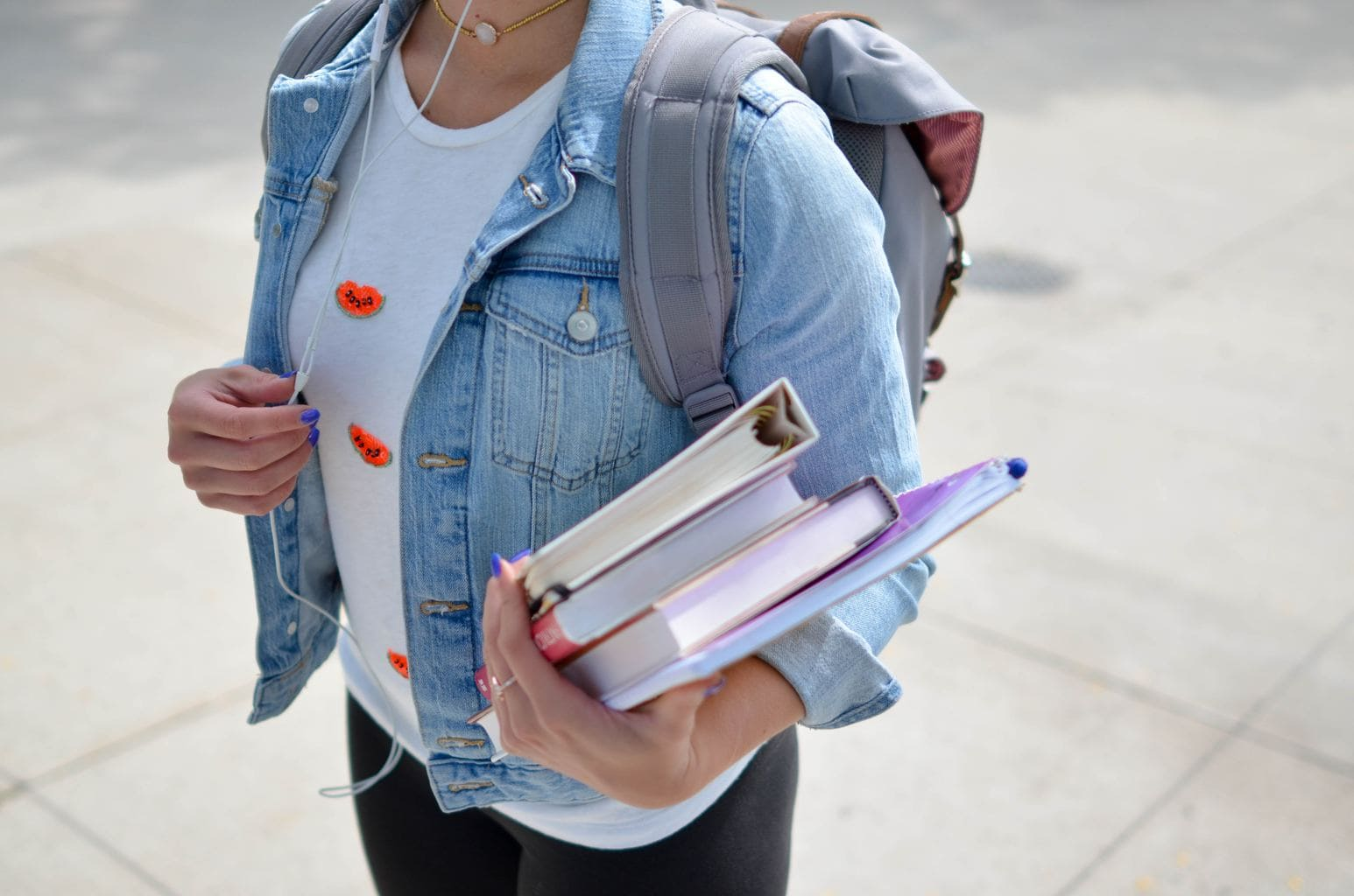 college girl with backpack carrying books