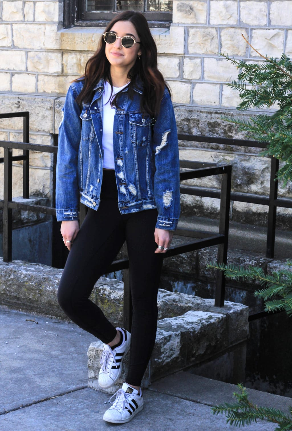 Kansas State University student Bailey wears a casual white tee with high-rise black leggings, a distressed, oversized denim jacket, worn-in Adidas all star sneakers, and round retro gold-rimmed sunglasses.