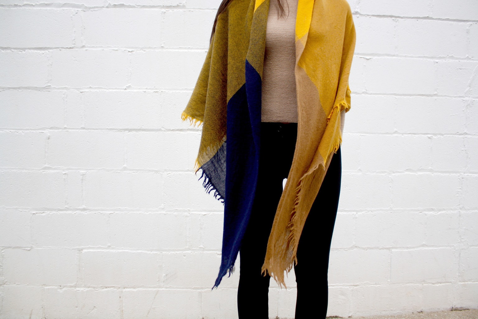 A college student at Western University wears a yellow and blue scarf as a shawl with leggings