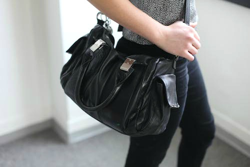 College student carrying black handbag