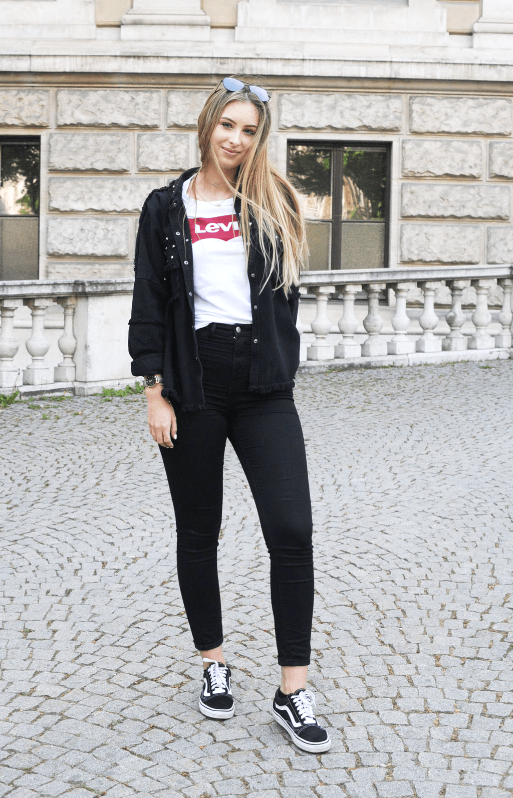 College student fashion at the University of Vienna - student Anika wears a Levi's vintage tee shirt, an oversized black jacket, black skinny jeans, and black and white Vans sneakers