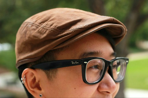 College student wearing a vintage hat and glasses