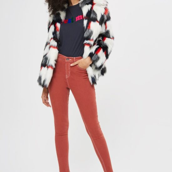 Woman wearing white, black, red, and gray faux-fur jacket, black t-shirt with multi-colored
