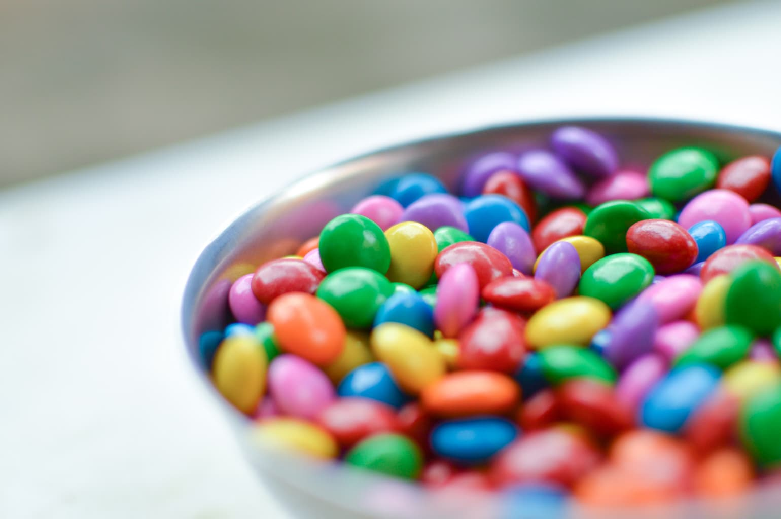 A bowl of colorful, round pieces of candy.