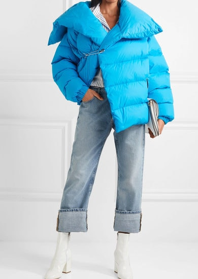Woman wearing bright blue oversized puffer coat with safety-pin closure over rolled-up jeans and striped button-up, with white patent block-heeled ankle boots and white oversized clutch