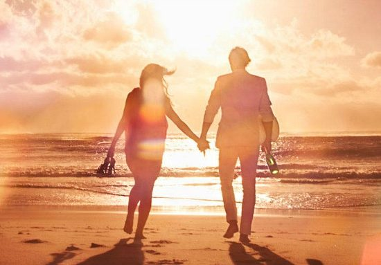 ELLE couple holding hands at beach