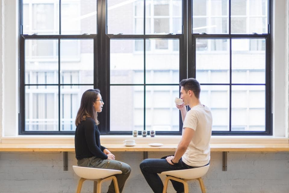 Man and woman in the city drinking coffee at a bar