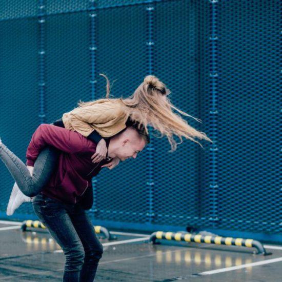 Girl on boy's back having fun in a parking lot