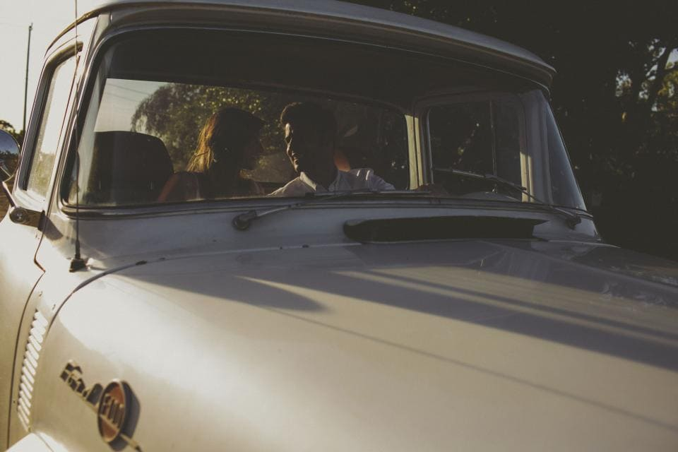 Couple sitting in white truck looking at each other