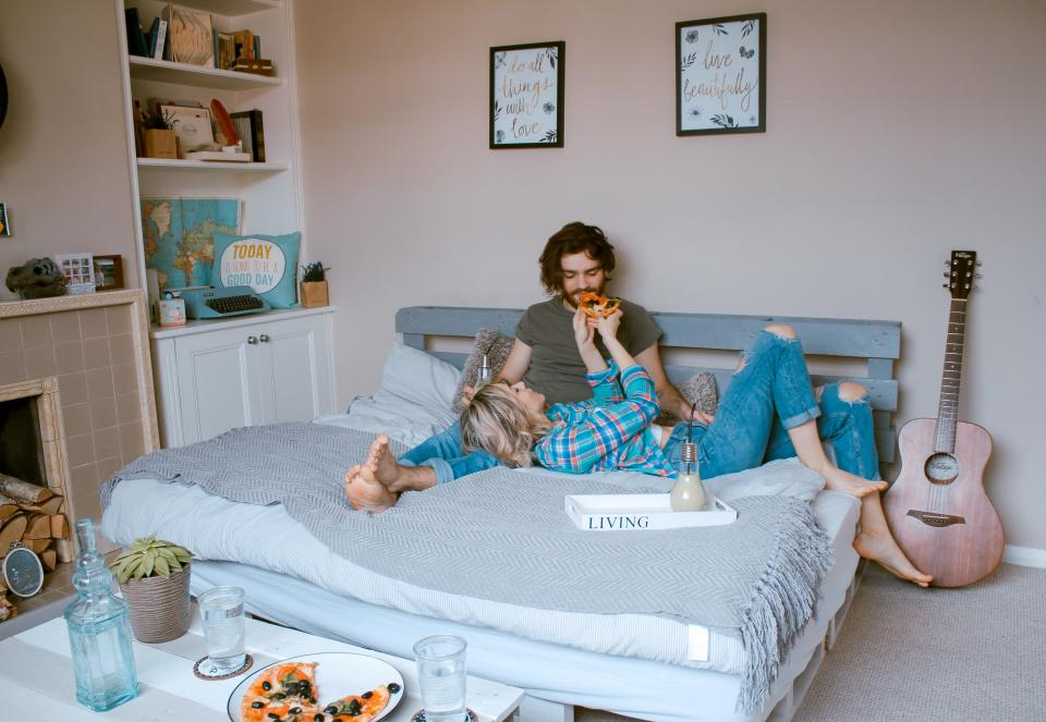 Woman feeding man pizza in bed