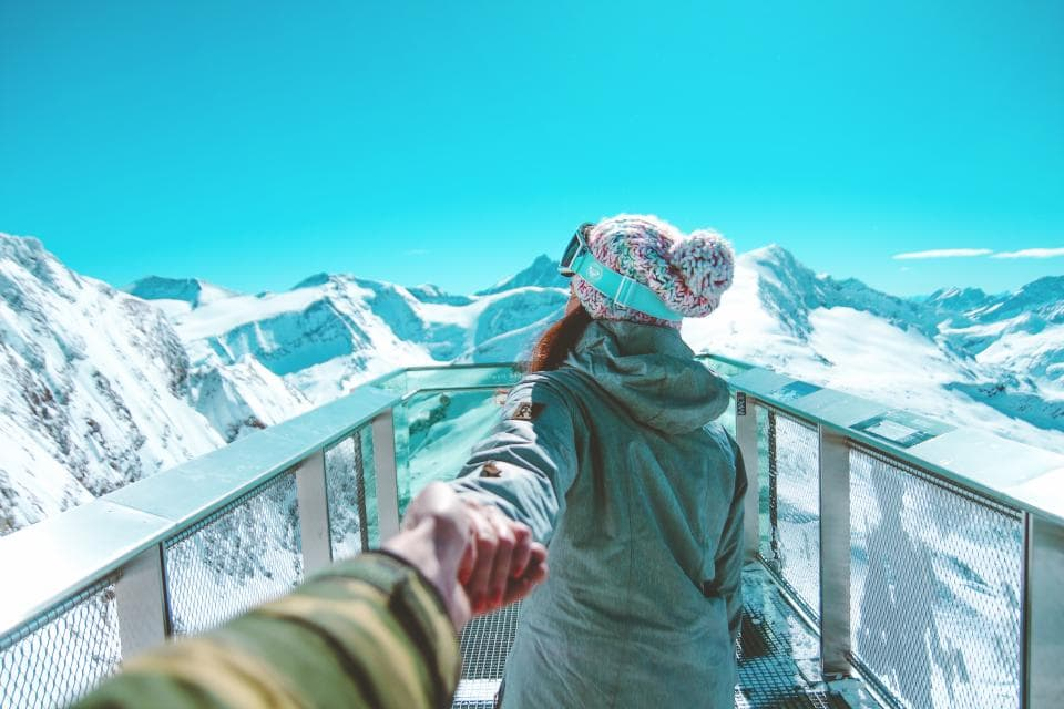 Girl holding hands with someone on a mountain