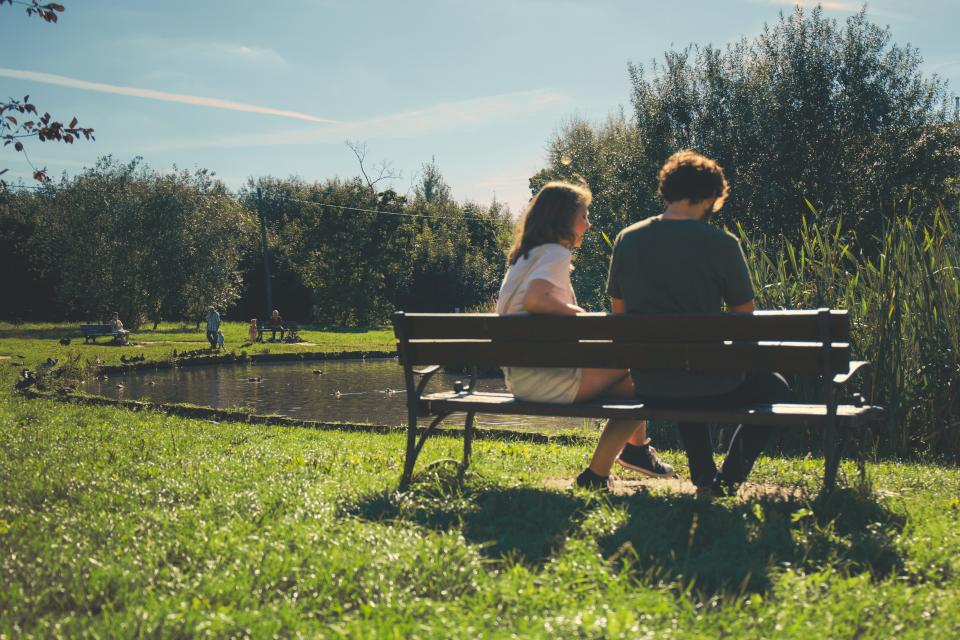 Man and woman sitting on a bench in the park