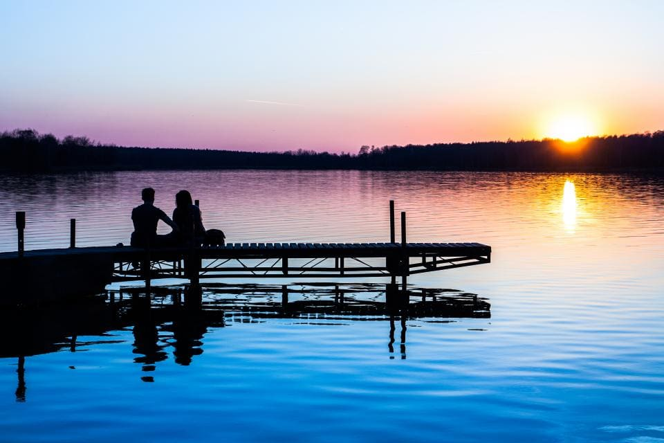 Couple on lake, sitting on pier, watching the sunset