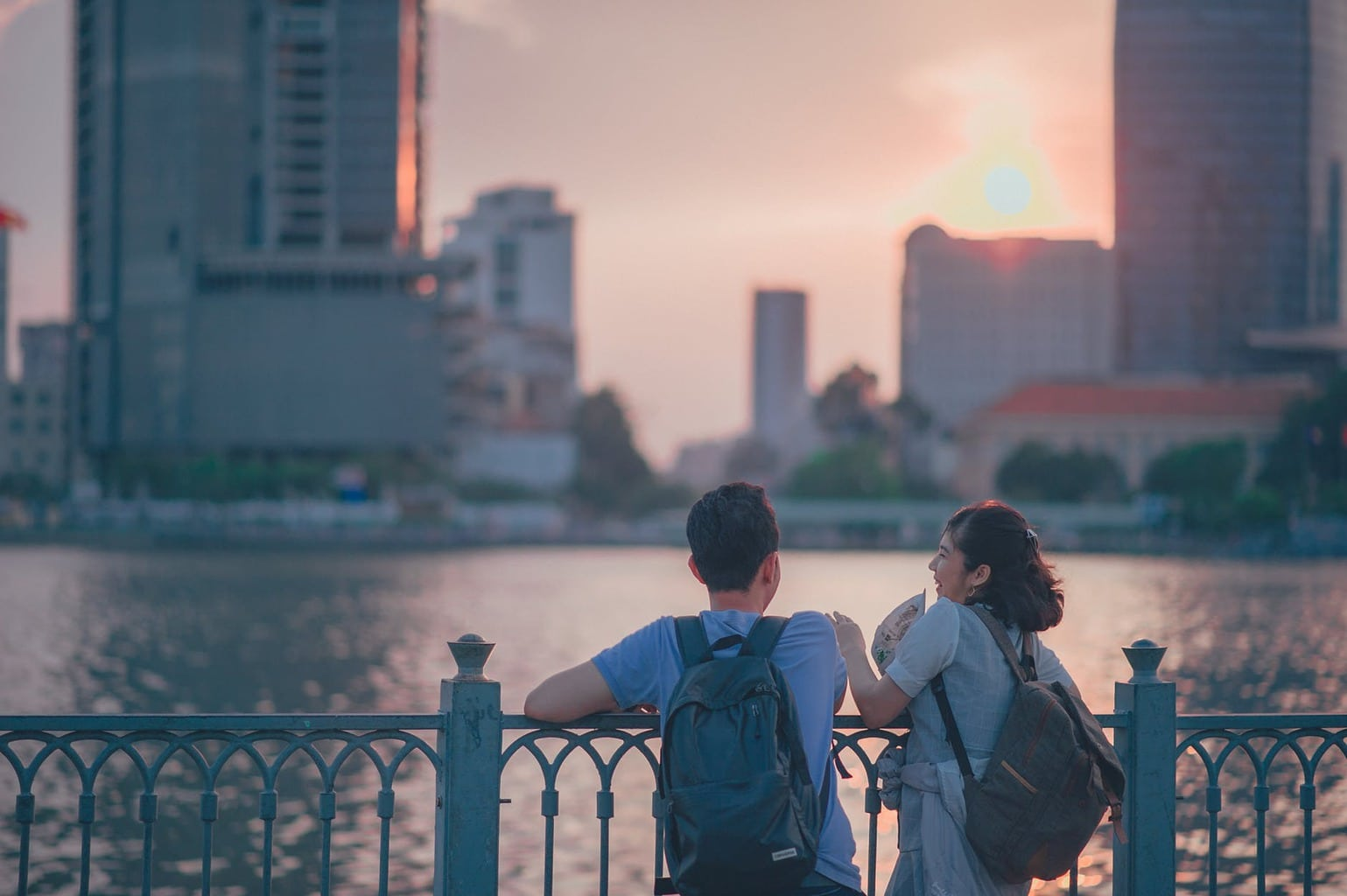 Boy and girl wearing backpacks having a conversation overlooking a river at sunset