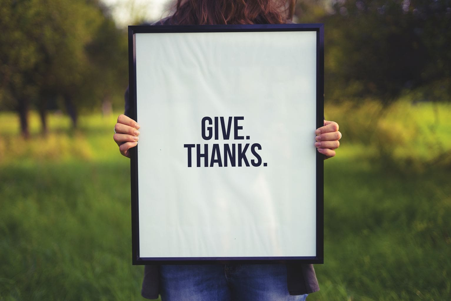 """Photo of woman standing outside and holding white framed sign that says """"GIVE. THANKS."""" in black capital letters."""