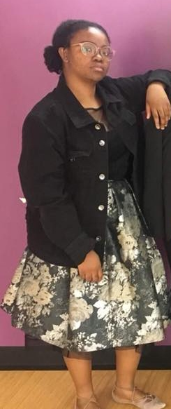 College student wearing glasses, an oversized denim jacket, and a wide skirt