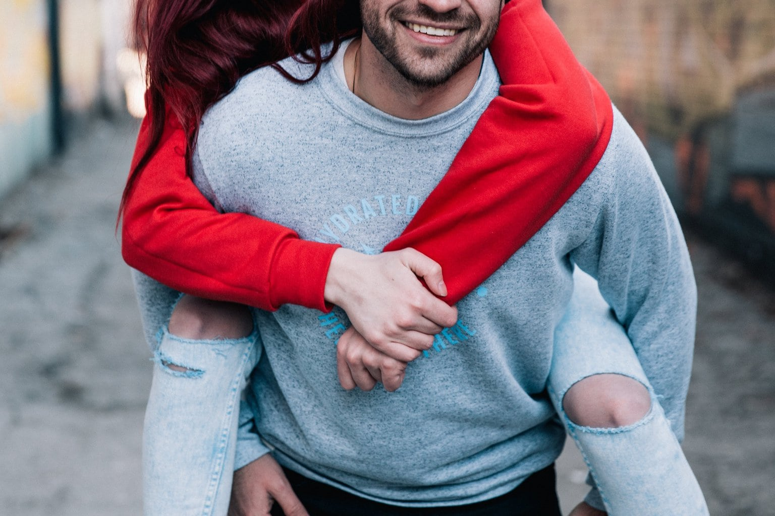 Photo of a couple on a date, with the boyfriend giving his girlfriend a piggyback ride