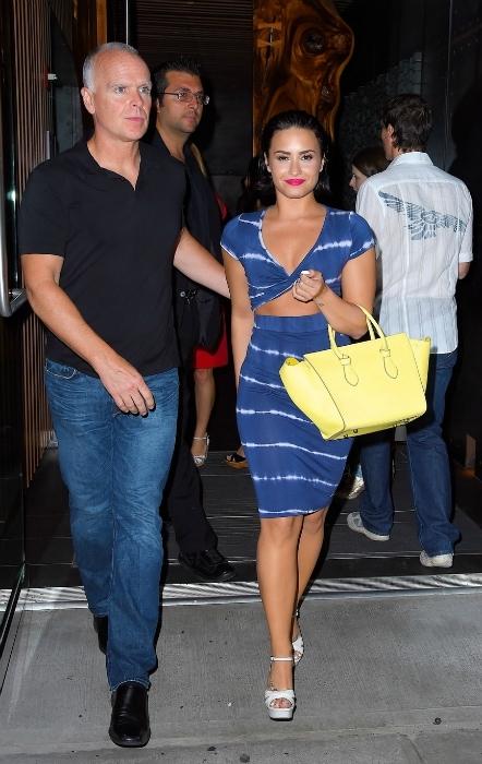 Demi Lovato wearing a blue cutout dress and yellow purse