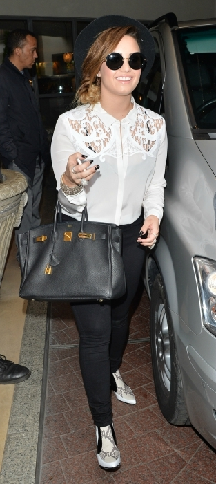 Demi Lovato wearing a lace button-up and black pants