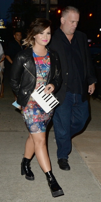 Demi Lovato wearing a printed dress and moto jacket