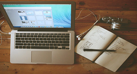 Desktop with laptop, journal, and camera
