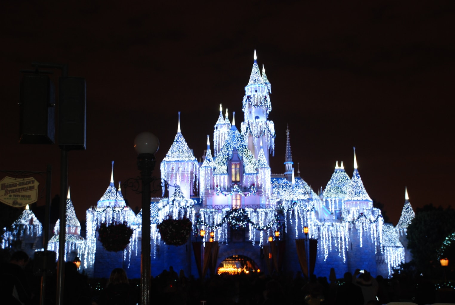 Disney castle decorated with white icicle lights for the holidays