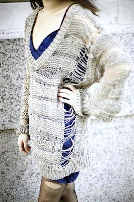 Distressed sweater worn over velvet dress