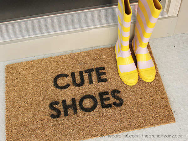 Photo of a doormat with striped yellow and pink rain boots on it.