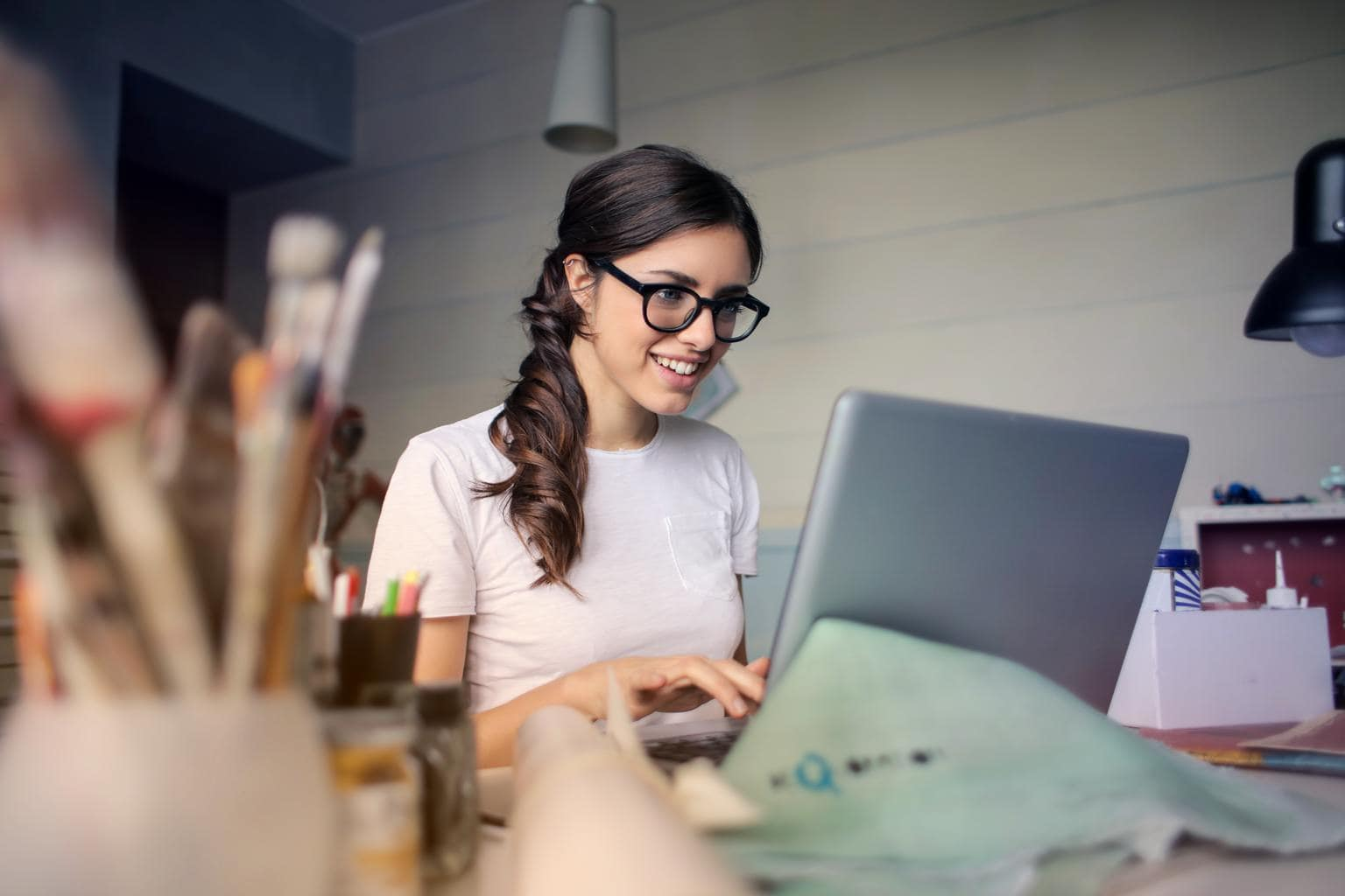 Photo of brunette girl with a ponytail and glasses using a computer.