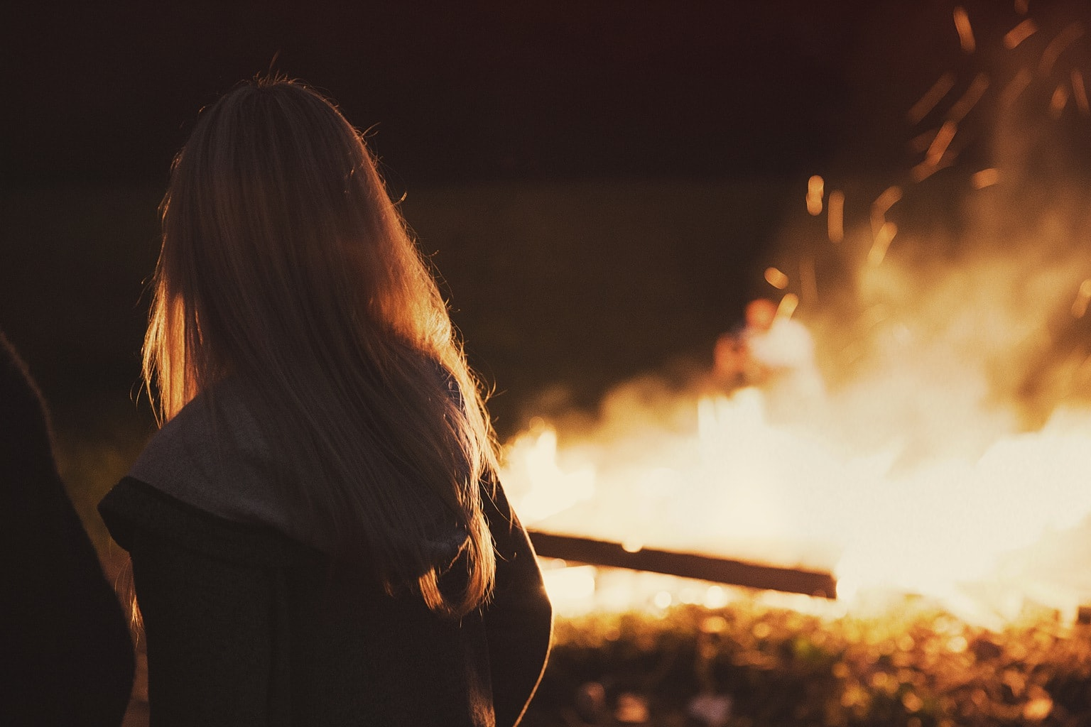 Woman in front of a fire