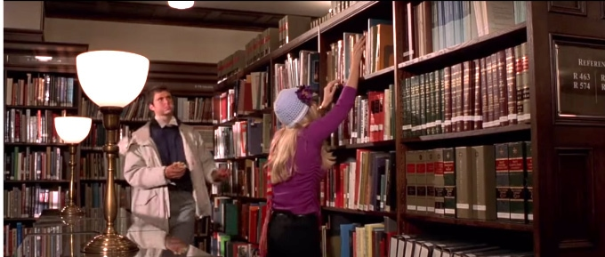 Elle Woods trying to get a book down from the shelf in the library - screenshot from the movie Legally Blonde