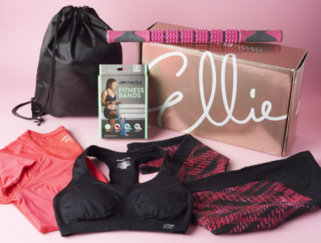 Ellie subscription box with various workout clothes surrounding it as well as a few fitness accessories.