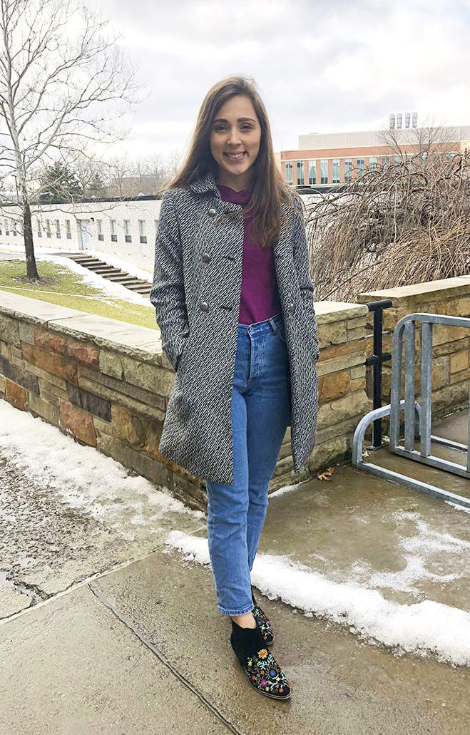 West Virginia University student wears a fashionable cold-weather outfit of an eggplant thrifted sweater, high-waisted mom jeans, and black embroidered floral booties with a black and white trench coat.