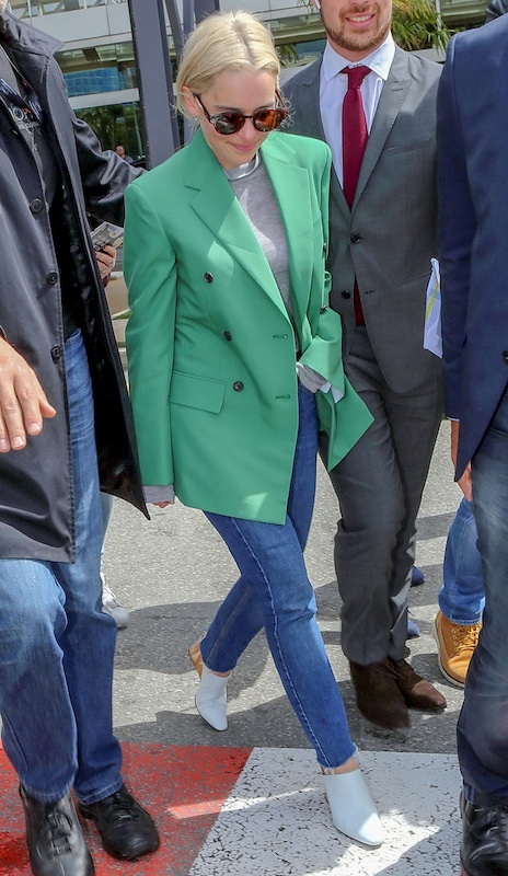 Emilia Clarke wearing a green double-breasted oversized blazer, a gray mock neck top, round tortoise sunglasses, medium wash straight leg jeans, and wedge mules