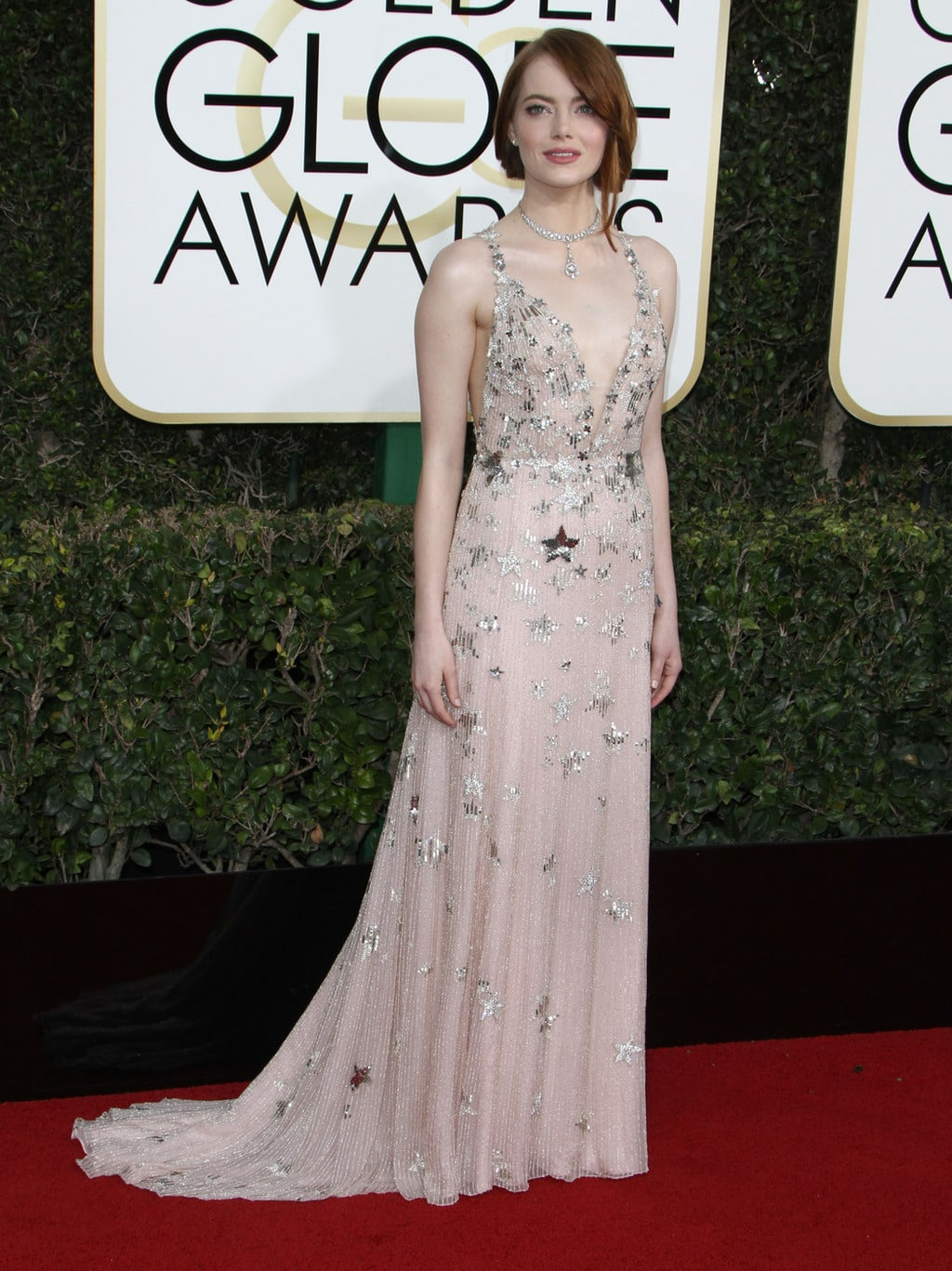Emma Stone wearing a light pink Valentino gown with silver stars on the 2017 Golden Globes red carpet