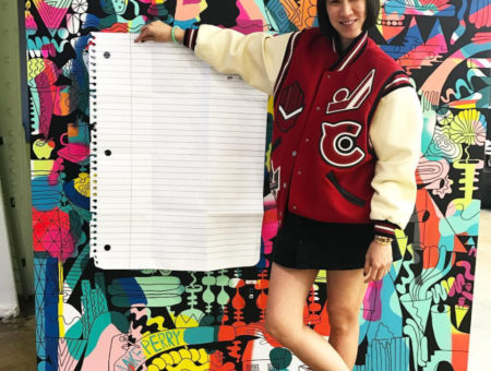 Eva Chen wearing a varsity jacket in front of a large piece of notebook paper