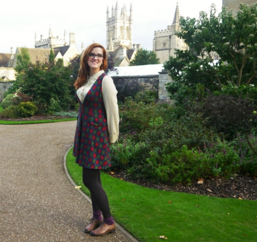 College student fashionista wearing a plaid dress, beige blouse, tights, and oxfords