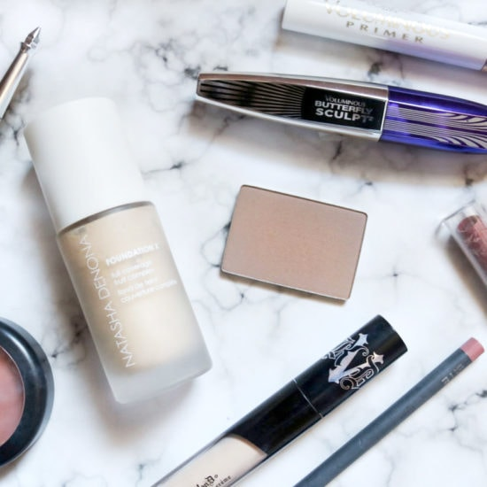 A college girl's favorite makeup products laid flat on a table