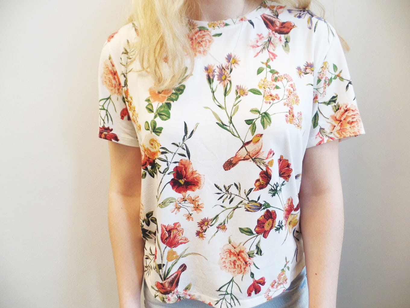 Veronica's short sleeve, crew neck top is covered in a green and orange floral pattern.